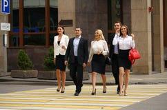 Groupe d'hommes d'affaires traversant la rue Image stock