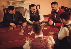 Groupe d'hommes de classe aristocratique jouant le tisonnier dans le club du ` s de messieurs Image libre de droits
