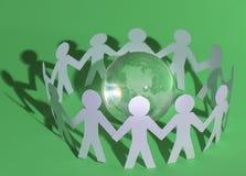 Groupe d'hommes de papier se tenant autour du globe en verre Image libre de droits