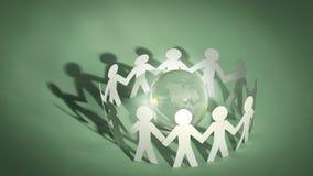 Groupe d'hommes de papier se tenant autour du globe en verre Image stock