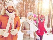 Groupe d'hommes et de femmes de sourire dans la forêt d'hiver Photographie stock libre de droits