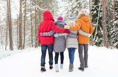 Groupe d'hommes et de femmes heureux dans la forêt d'hiver Photographie stock