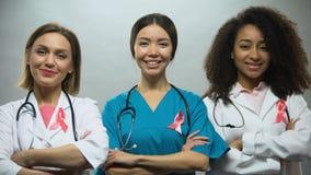 Groupe d'infirmières de sourire avec les rubans roses, conscience de cancer du sein, traitement banque de vidéos