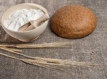 Groupe d'oreilles de blé, d'un bol de farine et de pain rond Photo stock