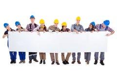 Groupe d'ouvriers et de femmes avec une bannière Photo stock