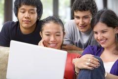 Groupe d'étudiant observant l'ordinateur portatif Photographie stock libre de droits