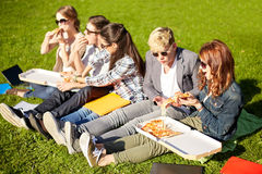 Groupe d'étudiants adolescents mangeant de la pizza sur l'herbe Image stock