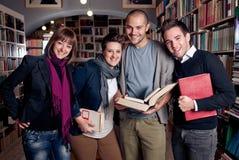 Groupe d'étudiants heureux à une bibliothèque Photos libres de droits