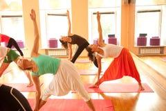 Groupe dans la pose de yoga (Uthittatriconasana) Image libre de droits