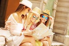 Groupe de amie employant la carte dans la ville Photographie stock