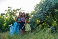 Groupe de amies avec des fleurs ayant l'amusement dehors Image stock