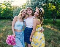 Groupe de amies avec des fleurs ayant l'amusement dehors Image libre de droits