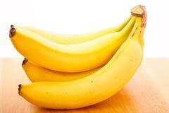 Groupe de bananes sur le Tableau en bois avec le fond blanc image stock