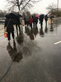 Groupe de banlieusards se dirigeant à la maison sous la pluie photos libres de droits