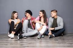 Groupe de beaux étudiants dans des vêtements sport utilisant des instruments, parlant et souriant tout en se reposant ensemble su Images libres de droits