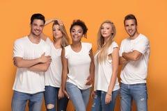 Groupe de beaux amis posant ensemble dans le studio Photo libre de droits