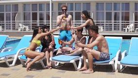 Groupe de beaux cocktails potables des jeunes et amusement de avoir à la piscine Tir au ralenti banque de vidéos
