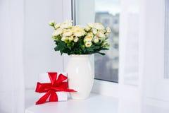 Groupe de beaux fleurs et boîte-cadeau roses sur un filon-couche de fenêtre Photos stock