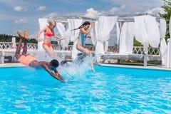 Groupe de beaux jeunes multi-ethniques semblant heureux tout en sautant dans la natation Images stock