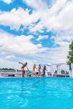 Groupe de beaux jeunes multi-ethniques semblant heureux tout en sautant dans la natation Image libre de droits