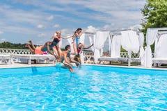 Groupe de beaux jeunes multi-ethniques semblant heureux tout en sautant dans la natation Images libres de droits