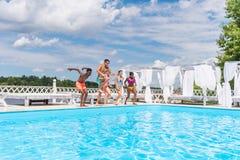 Groupe de beaux jeunes multi-ethniques semblant heureux tout en sautant dans la natation Photo libre de droits