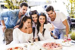 Groupe de beaux jeunes s'asseyant dans un restaurant et un taki Images libres de droits