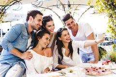 Groupe de beaux jeunes s'asseyant dans un restaurant et un taki Image libre de droits