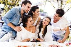 Groupe de beaux jeunes s'asseyant dans un restaurant et un taki Photographie stock libre de droits