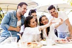 Groupe de beaux jeunes s'asseyant dans un restaurant et un taki Photos libres de droits