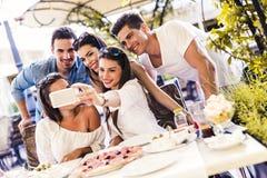 Groupe de beaux jeunes s'asseyant dans un restaurant et un taki Photo libre de droits