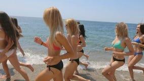 Groupe de beaux modèles dans des bikinis fonctionnant le long du rivage d'une plage banque de vidéos