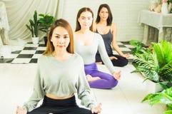 Groupe de belles femmes dans des classes de yoga et de m?ditation pour r?g?n?rer l'esprit et l'esprit, avec le concept de la rela photographie stock