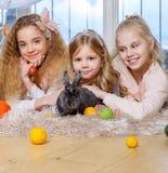 Groupe de belles petites filles se trouvant sur le tapis et jouant avec le lapin Photographie stock