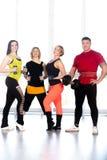 Groupe de bodybuilders sportifs positifs faisant la formation de poids dans g Images stock
