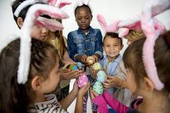 Groupe de bonheur d'enfants mignons et adorables chassant l'oeuf de pâques Image stock