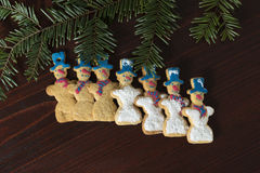 Groupe de bonhomme de neige de pain d'épice sur une table en bois Photos stock