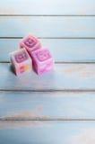 Groupe de bougies colorées de cube sur le plancher en bois Images stock
