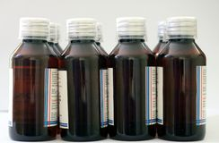 Groupe de bouteilles ambrines d'animal familier de médecine avec le chapeau transparent de dosage de 10 ml utilisé dans le secteu photographie stock libre de droits