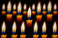 Groupe de brûlure jaune de lueur d'une bougie sur le noir Photo stock