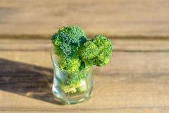 Groupe de brocoli vert frais en verre sur la fin en bois de table sur le fond d'un mur en pierre images libres de droits