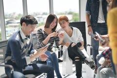 Groupe de businesspersons discutant et à l'aide des appareils électroniques Image stock