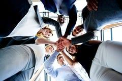 Groupe de cadres regardant en bas des mains ensemble photographie stock libre de droits