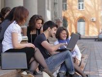 Groupe de camarades d'études avec les livres et l'ordinateur portable Images libres de droits