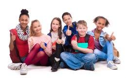 Groupe de camarades de classe s'asseyant sur le plancher Photographie stock libre de droits