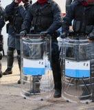 Groupe de cannettes de fil d'émeute avec des bâtons et des boucliers pendant le contrôle de sécurité Photographie stock libre de droits