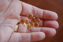Groupe de capsules claires de gel de vitamine ou pilules à disposition de femme image stock