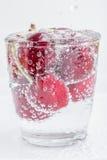 Groupe de cerises douces et de bulles mûres miroitant dans un verre de Photos stock