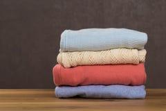 Groupe de chandails chauds tricot?s avec diff?rents mod?les de tricotage pli?s dans la pile sur la table en bois brune photographie stock libre de droits