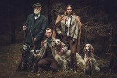 Groupe de chasseurs de multi-âge avec des chiens et des fusils de chasse dans un habillement traditionnel de tir, posant sur un f photo stock